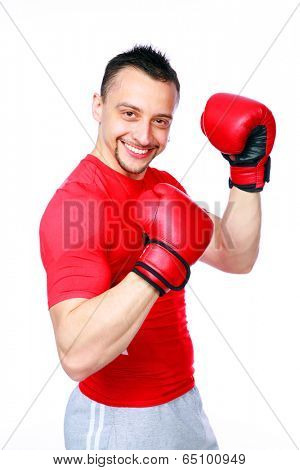 Smiling sportsman in boxing gloves standing over white background