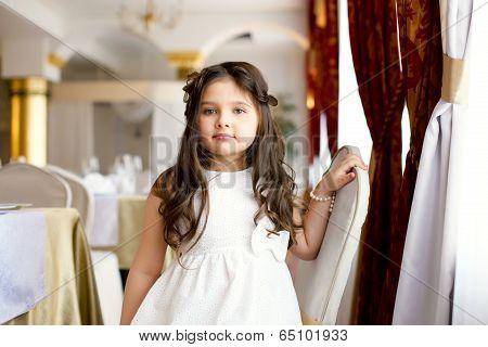 Beautiful little fashionista posing in restaurant