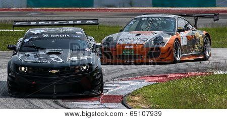 SEPANG, MALAYSIA - MAY 11, 2014: Tomas Enge in a Camaro GT3 car leads Vutthikorn Inthraphuvasak's Porsche 997 GT3R after turn 1 of the Sepang International Circuit at the Thailand Supercar GT3 race.