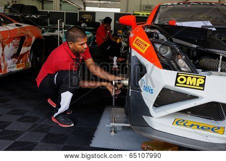 SEPANG, MALAYSIA - MAY 11, 2014: Unidentified team mechanics work on the cars for the Lamborghini Super Trofeo race, part of the Malaysian Super Series Rd 2 held at the Sepang International Circuit.