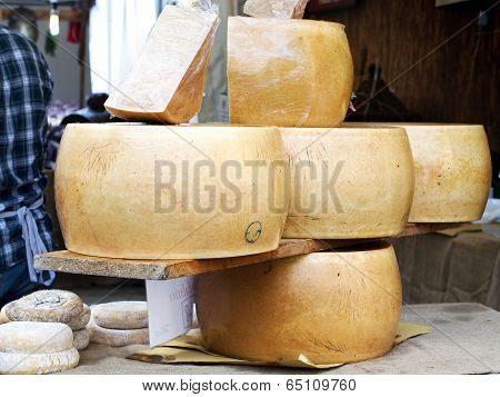 Large Blocks Of Italian Form Of Parmesan Cheese Exposed On A Table In  A Country Fair