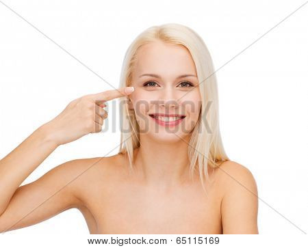 health and beauty concept - face of beautiful woman touching her eye area