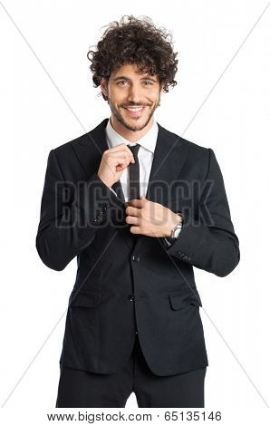Portrait Of Stylish Man Adjusting Necktie Isolated On White Background
