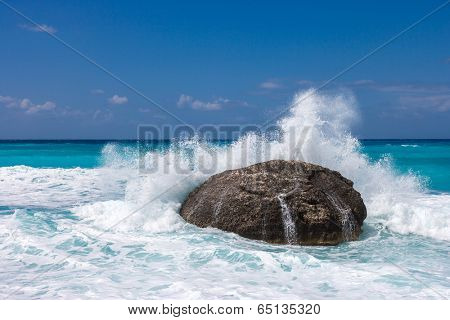 wild beach of the island of Lefkada in Greece with water crashing on the rocks