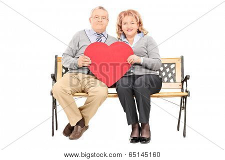 Lovely mature couple holding big red heart seated on bench isolated on white background
