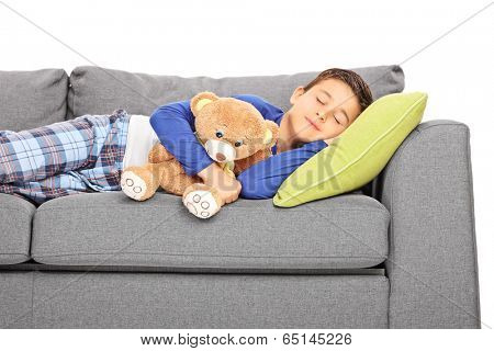 Little boy taking a nap on a couch isolated on white background