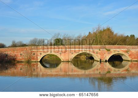 Large arched redbrick river bridge in suffolk
