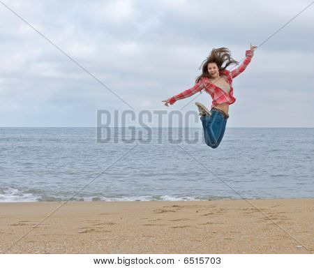 Teen girl jumping excitedly on the beach.