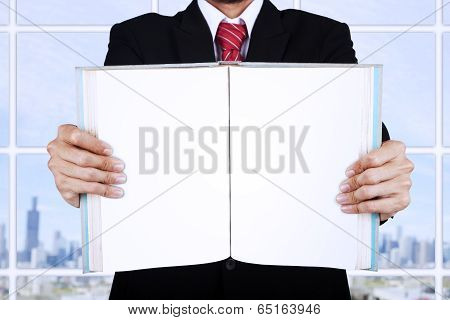 Businessman Holding Blank Open Book At Office