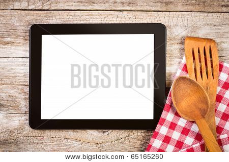 Tablet On Wooden Surface And Serving Spoons.