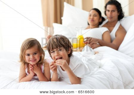 Happy Siblings Having Breakfast With Their Parents