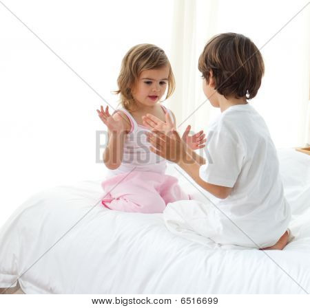 Cute Siblings Playing On The Bed