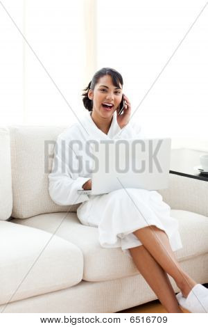 Smiling Woman On Phone Using A Laptop
