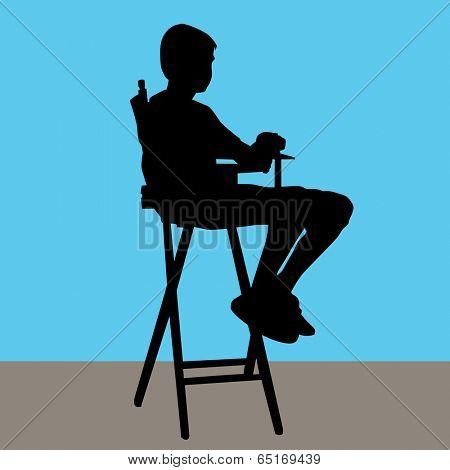 An image of a young male sitting in a director's chair.