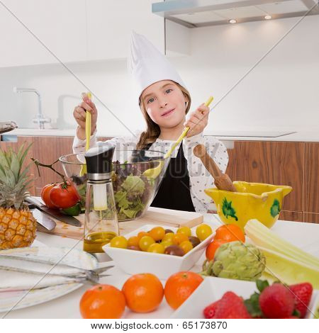 Blond kind girl junior chef on countertop preparing salad
