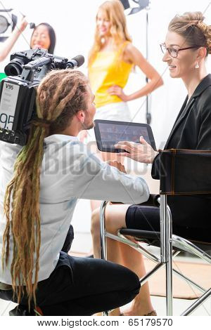 Director giving cameraman shoot or scene direction on set of a video production for TV, television or News