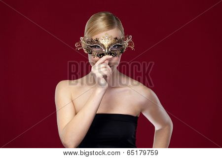 Beautiful woman with patterned masquerade mask, isolated on purple