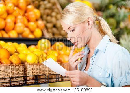 Girl reads shopping list near the heap of fruits lying in the braided baskets in the shop