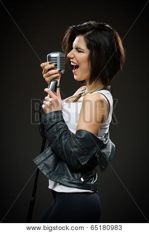 Side view of female rock singer wearing black jacket and keeping microphone on grey background. Concept of music and rave