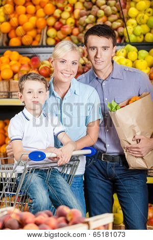 Happy family against shelves of fruits goes shopping. Father keeps a packet with fruits and son sits in the cart