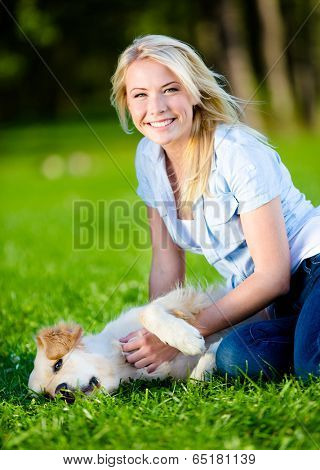 Woman strokes golden retriever lying on the green grass in the park