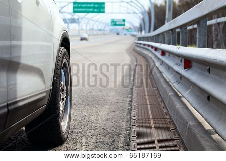 Car Standing On Wayside Of Highway With Road View At Distance