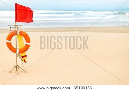 Life Saving Objects With Red Flag On Beach.