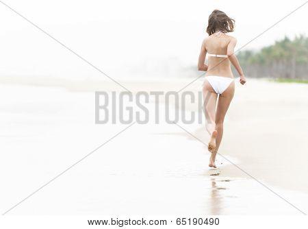 Pretty Woman Running On Wet Sand Along Beach.