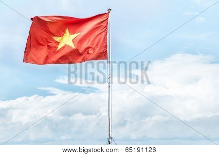 Red National Flag Of Vietnam Waving In Blue Sky.