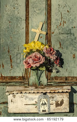Rustic old weathered and worn doorway with charming display of flowers and cross