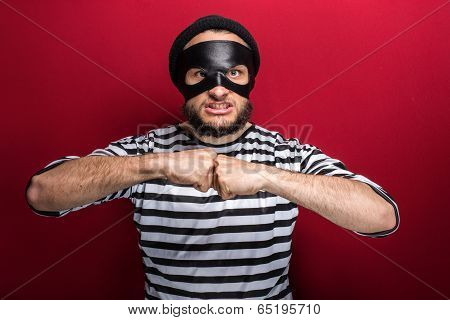 Portrait of a angry thief threaten with a fist