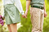 pic of jeans skirt  - Young couple in love walking in the spring park holding hands looking in the sunset - JPG