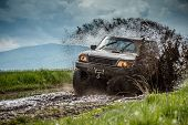 stock photo of headgear  - Jeep off road in muddy conditions - JPG