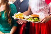 stock photo of diners  - Friends or couple eating fast food in American fast food diner - JPG