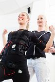 stock photo of stimulation  - Female personal trainer giving man ems electro muscular stimulation exercise - JPG