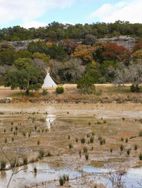 stock photo of tipi  - White traditional native american dwelling on the banks of a shallow river - JPG