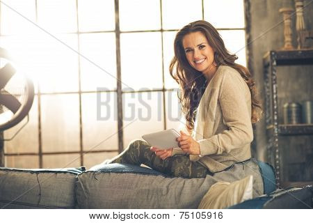 Portrait Of Happy Young Woman Using Tablet Pc In Loft Apartment