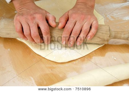 Hands On Rolling Pin Over Dough