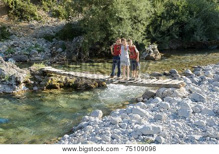 KELMEND, ALBANIA - AUGUST, 10: three smiling children are posing on a  wooden jumper that crosses a creek of Kelmend District in the north Albania. Shot in 2013
