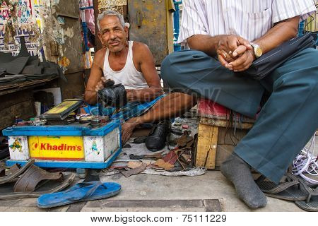 KOLKATA, INDIA - MARCH 14: Unidentified shoe shiner does his job at street of Kolkata on March 14, 2013. Lots of people make their living by doing this job in India.