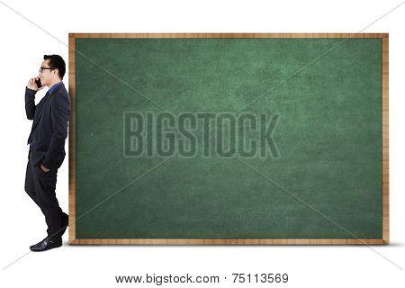 Businessman Leans On Empty Blackboard