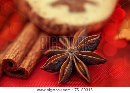 Star anise and cinnamon on red background, close up