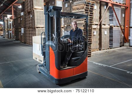 Fork lift operator drives through warehouse and is preparing the products for shipment