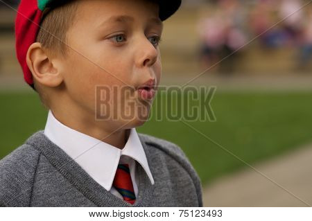Close-up Of Uniformed Schoolboy Blowing Out Cheeks