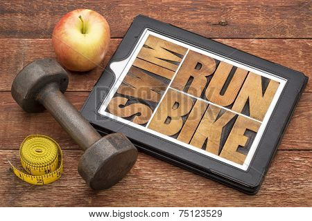 run, bike, swim - fitness or triathlon concept - word abstract in letterpress wood type on a digital tablet with a dumbbell, apple and tape measure