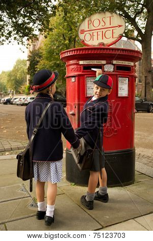 Schoolboy Turning While Posting Letter With Sister