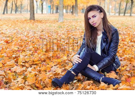 beautiful girl in rock style with bright makeup in white jacket and black pants and boots