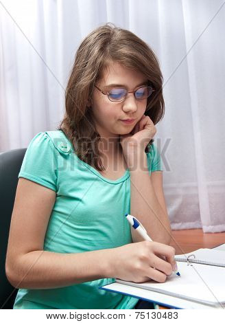 teenager girl writing in notebook at home.Portrait of a cute school girl at her desk