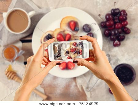 Woman taking a photo of breakfast with smartphone