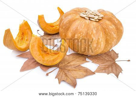 Autumn Vegetable And Yellow Pumpkin Seeds From It. On Yellow Leaves.